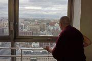 Его Святейшество Далай-лама смотрит на город из окна своей гостиницы. Саппоро, Япония. 3 апреля 2015 г. Фото: Джереми Рассел (офис ЕСДЛ)