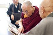 В университете Аичи Гакуен Его Святейшество Далай-лама беседует со старым другом и рассматривает фотографии своего первого визита в Японию, который состоялся в 1967 году. Нагоя, Япония. 7 апреля 2015 г. Фото: Тензин Джигме