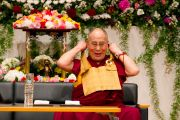 Его Святейшество Далай-лама поправляет на шее традиционную японскую сумку, перед тем как начать лекцию. Гифу, Япония. 8 апреля 2015 г. Фото: Тензин Джигме