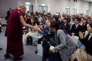 В конференц-центре Нагаракава Его Святейшество Далай-лама здоровается с людьми, которые будут смотреть его лекцию по видеотрансляции, поскольку в главном зале не хватило места для всех желающих. Гифу, Япония. 8 апреля 2015 г. Фото: Тензин Джигме