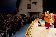 Его Святейшество Далай-лама приветствует аудиторию в начале второй сессии первого дня учений в университете Шова. Токио, Япония. 12 апреля 2015 г. Фото: Тензин Джигме