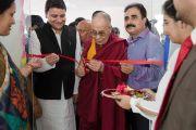 Его Святейшество Далай-лама перерезает красную ленточку на дверях нового информационного центра в Кангре. Химачал-Прадеш, Индия. 9 мая 2015 г. Фото: Тензин Чойджор (офис ЕСДЛ)