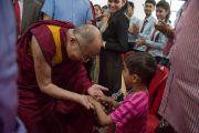 Его Святейшество Далай-лама здоровается с маленьким мальчиком перед началом своего краткого выступления в новом информационном центре. Кангра, штат Химачал-Прадеш, Индия. 9 мая 2015 г. Фото: Тензин Чойджор (офис ЕСДЛ)