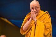 """Его Святейшество Далай-лама приветствует собравшихся в """"Тибетской детской деревне"""", перед тем как занять свое место на троне. Верхняя Дхарамсала, Индия. 29 мая 2015 г. Фото: Тензин Чойджор (офис ЕСДЛ)"""