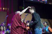 """Его Святейшество Далай-лама шутит с саксофонистом Энди Керком после его выступления в первый день саммита """"Глобальное сострадание"""" на сцене Хонда-центра. Аннахайм, штат Калифорния, США. 5 июля 2015 г. Фото: Тензин Чойджор (офис ЕСДЛ)"""