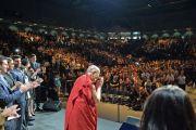 """Его Святейшество Далай-лама приветствует публику перед началом заключительной сессии саммита """"Глобальное сострадание"""" в Университете Калифорнии. Ирвайн, штат Калифорния, США. 7 июля 2015 г. Фото: Сонам Зоксанг"""