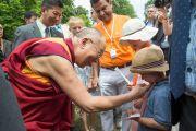 Его Святейшество Далай-лама здоровается со своим юным поклонником в висбаденском Курпарке. Висбаден, Гессен, Германия. 12 июля 2015 г. Фото: Мануэль Бауэр