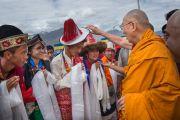 Его Святейшество Далай-лама рассматривает головной убор одного из учеников школы Джамьянг. Ле, Ладак, штат Джамму и Кашмир, Индия. 28 июля 2015 г. Фото: Тензин Чойджор (офис ЕСДЛ)