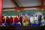 Его Святейшество Далай-лама и почетные гости стоя слушают гимны Индии и Тибета на официальной церемонии в честь 26-й годовщины вручения Его Святейшеству Нобелевской премии мира. Хунсур, штат Карнатака, Индия. 10 декабря 2015 г. Фото: Тензин Чойджор (офис ЕСДЛ)