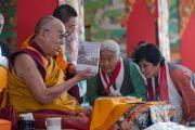 Его Святейшество Далай-лама представляет собравшимся новую книгу с автобиографией Джампы Калдена в начале шестого дня учений по 18 коренным текстам и комментариям традиции Ламрим в монастыре Ташилунпо. Билакуппе, штат Карнатака, Индия. 25 декабря 2015 г. Фото: Тензин Чойджор (офис ЕСДЛ)