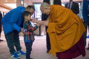 Его Святейшество Далай-лама здоровается с маленьким мальчиков по дороге в зал, где будут проходить учения. Осака, Япония. 10 мая 2016 г. Фото: Тензин Чойджор (офис ЕСДЛ)