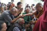 По прибытии в главный тибетский храм Его Святейшество Далай-лама приветствует верующих, собравшихся на учения по поэме «Бодхичарья-аватара», организованные по просьбе буддистов индийской ассоциации «Наланда Шикша». Дхарамсала, Индия. 7 июня 2016 г. Фото: Тензин Чойджор (офис ЕСДЛ)