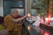 Его Святейшество Далай-лама возжигает масляную лампаду у алтаря в зале собраний храма Дрепунг Лачи. Мундгод, штат Карнатака, Индия. 1 июля 2016 г. Фото: Тензин Чойджор (офис ЕСДЛ)