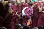 Тибетец из местного тибетского сообщества в традиционном одеянии вместе с монахами ожидает начала молебна о долгой жизни Его Святейшества Далай-ламы, проводимого в монастыре Дрепунг в честь 81-летия Далай-ламы. Мундгод, штат Карнатака, Индия. 6 июля 2016 г. Фото: Тензин Чойджор (офис ЕСДЛ)