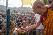 Его Святейшество Далай-лама приветствует юных слушателей по прибытии на площадку Шивацель в начале второго дня учений по поэме Шантидевы «Бодхичарья-аватара». Ле, Ладак, штат Джамму и Кашмир, Индия. 19 августа 2016 г. Фото: Тензин Чойджор (офис ЕСДЛ)