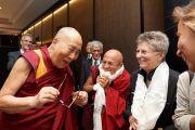 Его Святейшество Далай-лама приветствует участников конференции «Ум и жизнь», собравшихся рано утром в холле его отеля. Брюссель, Бельгия. 8 сентября 2016 г. Фото: Оливье Адам