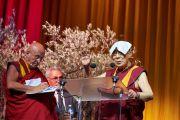 Личный переводчик Его Святейшества Далай-ламы на французский язык Матье Рикар делает записи, в то время как Его Святейшество выступает с публичной лекцией, накрыв голову полотенцем, чтобы защититься от жаркого света прожекторов. Брюссель, Бельгия. 11 сентября 2016 г. Фото: Оливье Адам