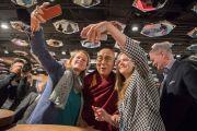 Местные жители фотографируются с Его Святейшеством Далай-ламой, прибывшим в свой отель в Цюрихе. Цюрих, Швейцария. 13 октября 2016 г.