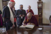 Его Святейшество Далай-лама расписывается в книге почетных гостей во время визита в резиденцию кардинала Милана Анджело Сколы. Милан, Италия. 20 октября 2016 г. Фото: Тензин Чойджор (офис ЕСДЛ)