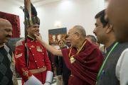 Его Святейшество Далай-лама шутливо приветствует гвардейца в парадной форме в культурном центре Раштрапати-Бхавана. Нью-Дели, Индия. 10 декабря 2016 г. Фото: Тензин Чойджор (офис ЕСДЛ)
