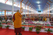 Его Святейшество Далай-лама машет рукой слушателям в начале учений в первый день посвящения Калачакры. Бодхгая, штат Бихар, Индия. 2 января 2017 г. Фото: Тензин Чойджор (офис ЕСДЛ)