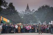 Ступа Махабодхи виднеется сквозь туман за спинами людей, выстроившихся вдоль дороги, чтобы поприветствовать Его Святейшество Далай-ламу, направляющегося из своей резиденции к площадке проведения посвящения Калачакры. Бодхгая, штат Бихар, Индия. 2 января 2017 г. Фото: Тензин Чойджор (офис ЕСДЛ)