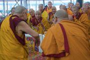 Его Святейшество Далай-лама приветствует монахов, сидящих на сцене, в начале первого дня учений, предваряющих посвящение Калачакры. Бодхгая, штат Бихар, Индия. 5 января 2017 г. Фото: Тензин Чойджор (офис ЕСДЛ)