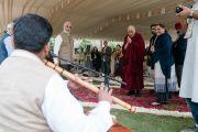По прибытии на место учений, организованных по просьбе фонда «Видьялока», Его Святейшество Далай-лама останавливается, чтобы послушать музыканта, исполняющего на флейте прекрасную мелодию. Нью-Дели, Индия. 4 февраля 2017 г. Фото: Тензин Чойджор (офис ЕСДЛ)