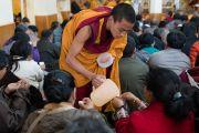 Монах раздает верующим освященную воду во время посвящения Авалокитешвары, даруемого Его Святейшеством Далай-ламой. Дхарамсала, Индия. 14 марта 2017 г. Фото: Тензин Чойджор (офис ЕСДЛ)