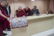 Его Святейшество Далай-лама подписывает традиционную танку с изображением Будды Шакьямуни и 17 пандит Наланды, преподнесенную им в дар университету Нава Наланда Махавихара. Раджгир, штат Бихар, Индия. 18 марта 2017 г. Фото: Тензин Чойджор (офис ЕСДЛ)
