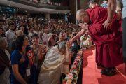Его Святейшество Далай-лама приветствует слушателей, поднявшись на сцену центра исполнительских искусств Индийской телевизионной академии (ИТА). Гувахати, штат Ассам, Индия. 1 апреля 2017 г. Фото: Тензин Чойджор (офис ЕСДЛ)