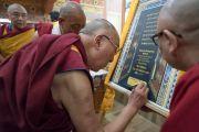 Его Святейшество Далай-лама подписывает постер в знак открытия Гималайского буддийского семинара, организованного в монастыре Тхупсунг Дхаргьелинг. Диранг, штат Аруначал-Прадеш, Индия. 5 апреля 2017 г. Фото: Тензин Чойджор (офис ЕСДЛ)