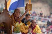 Его Святейшество Далай-лама держит книгу с произведением геше Лангри Тангпы «Восемь строф о преобразовании ума», обращаясь к верующим с просьбой следить за текстом во время учений. Диранг, штат Аруначал-Прадеш, Индия. 6 апреля 2017 г. Фото: Тензин Чойджор (офис ЕСДЛ)