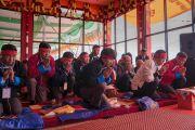 Надев красные ритуальные повязки, гости, сидящие на сцене, слушают наставления Его Святейшества Далай-ламы во время посвящения Авалокитешвары. Таванг, штат Аруначал-Прадеш, Индия. 9 апреля 2017 г. Фото: Тензин Чойджор (офис ЕСДЛ)