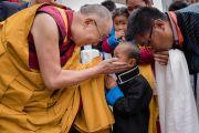 Его Святейшество Далай-лама приветствует маленького мальчика по прибытии на площадку учений при храме Йига Чойзин. Таванг, штат Аруначал-Прадеш, Индия. 9 апреля 2017 г. Фото: Тензин Чойджор (офис ЕСДЛ)