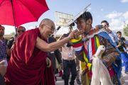 Его Святейшество Далай-лама шутливо приветствует юного танцора по прибытии в Тибетскую детскую деревню S.O.S в Чогламсаре. Ле, Ладак, штат Джамму и Кашмир, Индия. 25 июля 2017 г. Фото: Тензин Чойджор (офис ЕСДЛ)