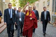 По дороге к машине Его Святейшество Далай-лама машет рукой местным жителям, выглядывающим из окон, чтобы увидеть тибетского духовного лидера. Пиза, Италия. 20 сентября 2017 г. Фото: Olivier Adam.