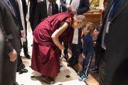Его Святейшество Далай-лама шутливо приветствует маленького мальчика на выходе из гостиницы. Рига, Латвия. 24 сентября 2017 г. Фото: Тензин Чойджор (офис ЕСДЛ)