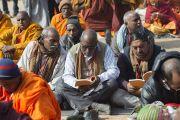 Слушатели следят за текстом во время первого дня учений Его Святейшества Далай-ламы, на которые собралось более 50 000 человек. Бодхгая, штат Бихар, Индия. 5 января 2018 г. Фото: Лобсанг Церинг.