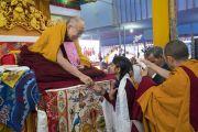 Одна из школьниц преподносит открытку в знак благодарности Его Святейшеству Далай-ламе после того, как ее группа прочитала Сутру сердца на санскрите в начале второго дня учений, организованных по просьбе индийских буддистов. Бодхгая, штат Бихар, Индия. 6 января 2018 г. Фото: Лобсанг Церинг.