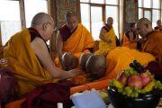 Его Святейшество Далай-лама благословляет монахов в ходе церемонии дарования полных монашеских обетов, организованной в новом зале собраний тибетского храма. Бодхгая, штат Бихар, Индия. 12 января 2018 г. Фото: дост. Тензин Джампель.
