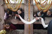 Паломники выглядывают из-за каменной ограды в надежде хоть мельком увидеть Его Святейшество Далай-ламу, совершающего обход вокруг храма Махабодхи. Бодхгая, штат Бихар, Индия. 13 января 2018 г. Фото: Тензин Чойджор.