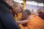 Поднявшись на сцену в павильоне Калачакры в начале заключительного дня учений, Его Святейшество Далай-лама приветствует одного из старших монахов. Бодхгая, штат Бихар, Индия. 16 января 2018 г. Фото: Мануэль Бауэр.