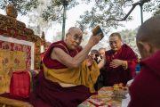 Его Святейшество Далай-лама держит символические изображения просветленных тела, речи и ума в начале молебна у ступы Махабодхи. Бодхгая, штат Бихар, Индия. 17 января 2018 г. Фото: Тензин Чойджор.