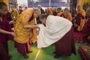 Его Святейшество Далай-лама приветствует Восера Ринпоче, поднявшись на сцену павильона Калачакры перед началом посвящения Ямантаки 13-ти божеств. Бодхгая, штат Бихар, Индия. 19 января 2018 г. Фото: Мануэль Бауэр.