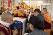 Перед началом посвящения Ямантаки 13-ти божеств основные спонсоры учений преподносят Его Святейшеству Далай-ламе символические изображения просветленных тела, речи и ума. Бодхгая, штат Бихар, Индия. 19 января 2018 г. Фото: Мануэль Бауэр.