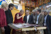 Во время перерыва между сессиями первого дня XXXIII конференции института «Ум и жизнь» Его Святейшество Далай-лама показывает ученым книгу с репродукциями тибетской настенной живописи. Дхарамсала, Индия. 12 марта 2018 г. Фото: Тензин Чойджор.