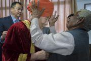 Его Святейшеству Далай-ламе помогают надеть традиционный тюрбан перед началом 1-й церемонии вручения дипломов в Центральном университете Джамму. Джамму, штат Джамму и Кашмир, Индия. 18 марта 2018 г. Фото: Тензин Чойджор.