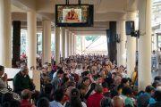 Верующие смотрят прямую трансляцию благословения на практику шестислоговой мантры Авалокитешвары, даруемого Его Святейшеством Далай-ламой в главном тибетском храме. Дхарамсала, Индия. 16 мая 2018 г. Фото: Тензин Пунцог.