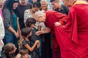 Его Святейшество Далай-лама шутливо приветствует детей во время встречи с туристами в главном тибетском храме. Дхарамсала, Индия. 19 мая 2018 г. Фото: Тензин Чойджор.